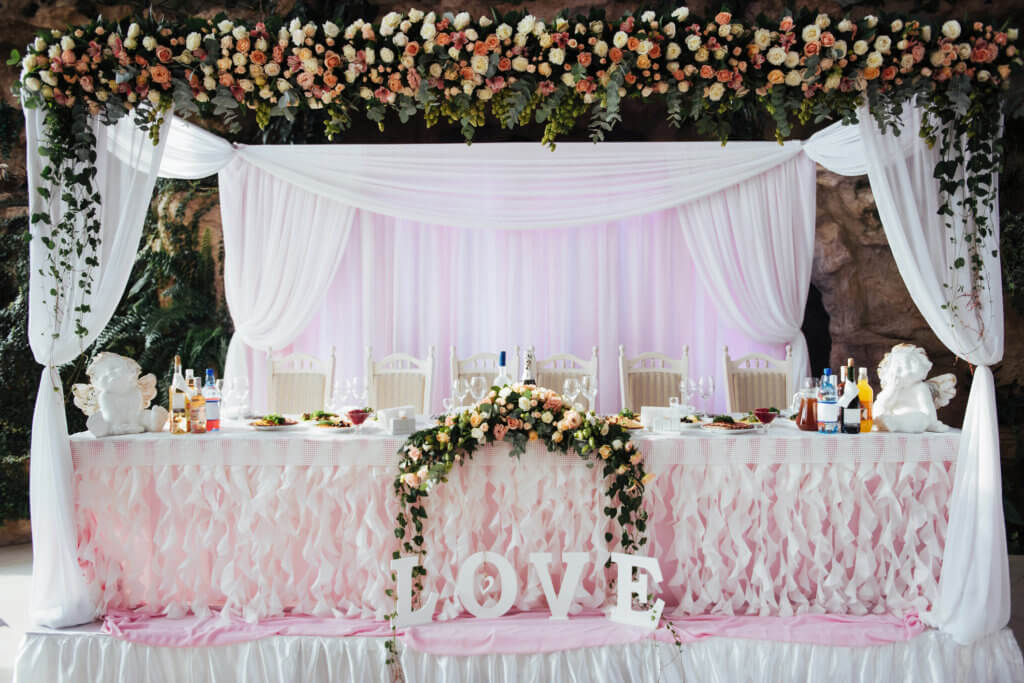 elegant bridal table decorated with flowers and love sign